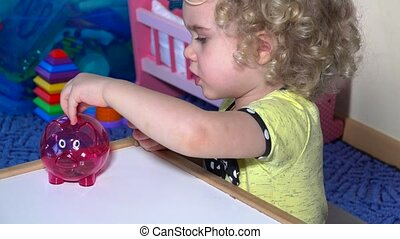 Young child start saving money for future. Girl with coins in piggy bank