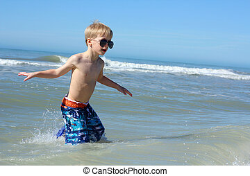 Young Child Walking in the Ocean Water