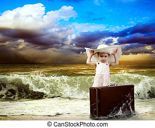 Young child with baggage on the tropical beach