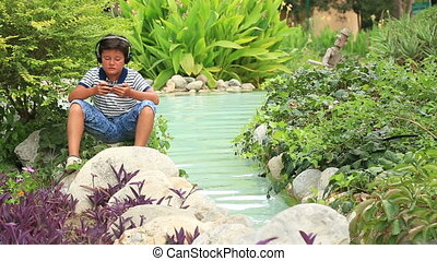 Young child with headphone relaxing at the park