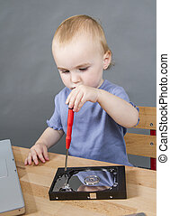 child working at open hard drive in grey background with laptop computer. vertical image