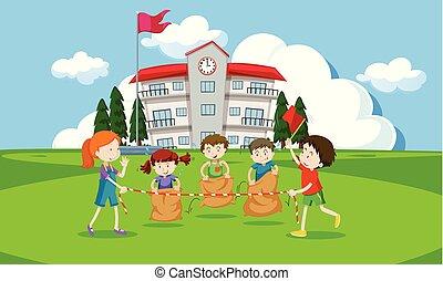Young children having a potato sack race