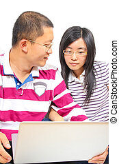 Young chinese couple sitting with a laptop