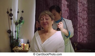 Young chinese doctor doing massage to a senior woman - Crane...