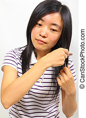 Young chinese woman brushing her hair