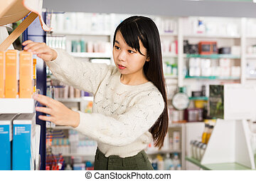 Young chinese woman near counter in pharmacy