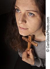 Young christian girl with cross looking up