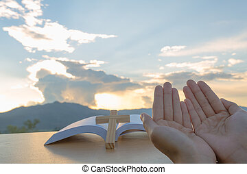 Young christian woman hands open palm up worship and praying to god at sunrise, Christian Religion concept background.