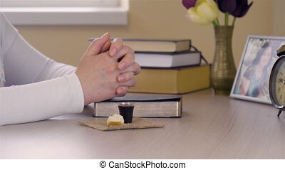 Young Christian woman taking the Lord's Supper Communion after prayer. Close up dolly shot.