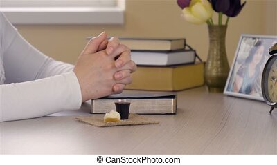 Young Christian woman praying and taking Communion