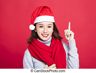 young christmas woman wearing santa hat and pointing up