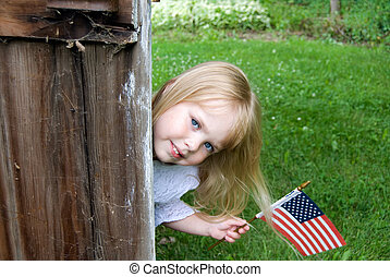 Young Citizen - Little girl with flag by barn door.