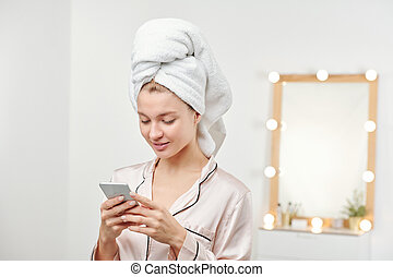 Young clean woman with soft white towel on head scrolling in smartphone