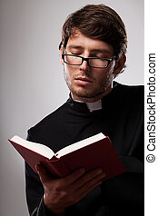 Young clergyman studying a Bible - Young vicar wearing black...
