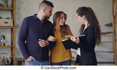 Young clients are looking at documents and discussing deal conditions with real estate broker while standing inside new apartment. Relocation and purchase concept.