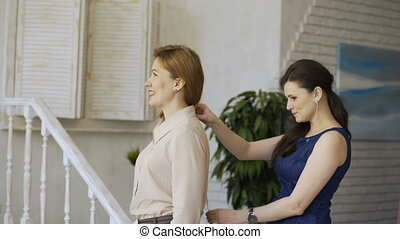 Young clother designer woman shows the cloth to her client in tailor studio