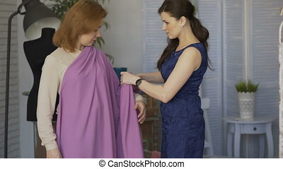 Young clother designer woman trying on cloth to her client in tailor studio