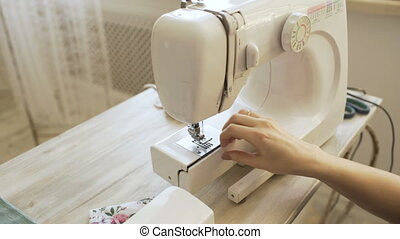 Young clothing designer and seamstress woman works with...