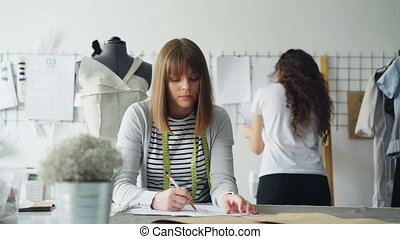 Young clothing designer is busy drawing sketch with pencil while her colleague is watching pictures pinned on wall in design studio. Creative thinking concept.