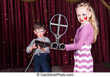 Young Clowns Holding Large Gun on Stage