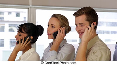 Young colleagues standing in a row while phoning in the...