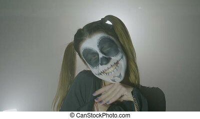 Young college female student wearing halloween makeup trying...