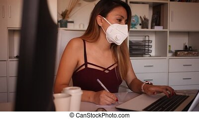 Young colombian woman in mask working with laptop at the office table