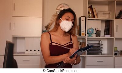 Young Colombian woman manager in mask holding clipboard in modern office