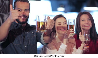 Young company showing thumb up and  lifts up a glass of beer