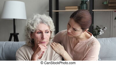 Young compassionate woman supporting depressed middle aged mother, giving psychological help. Worried grownup daughter cuddling, making peace with stressed mature senior retired mommy at home.