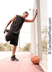 Young concentrated african basketball player making sport exercises