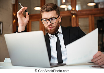 Young concentrated bearded businessman in formalwear looking at laptop screen holding papers while sitting at workplace