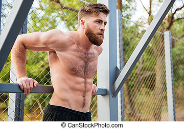 Young concentrated bearded strong man doing sports exercises