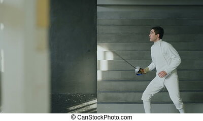 Young concentrated fencer man practice fencing exercises and...