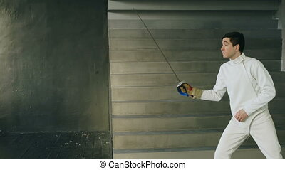 Young concentrated fencer man training fencing exercise in...
