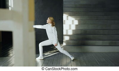 Young concentrated fencer woman practice fencing exercises...