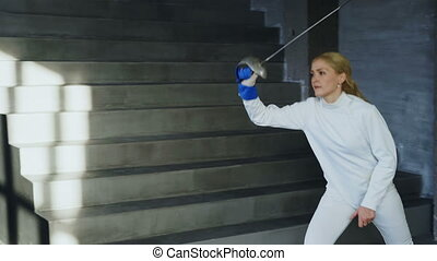 Young concentrated fencer woman training fencing exercise in...