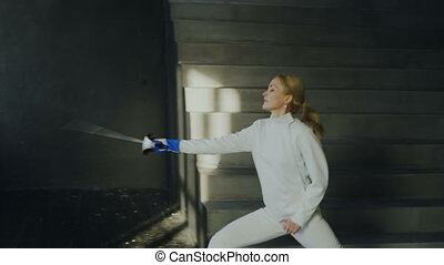 Young concentrated fencer woman training fencing attack...