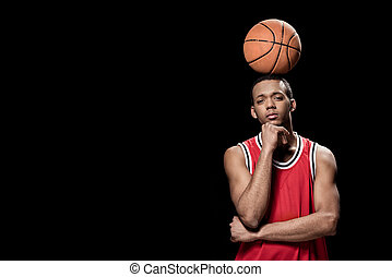Young confident basketball player posing with ball on head on black