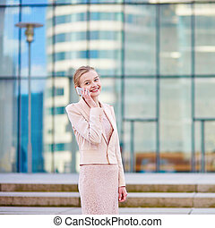 Young confident business woman using phone