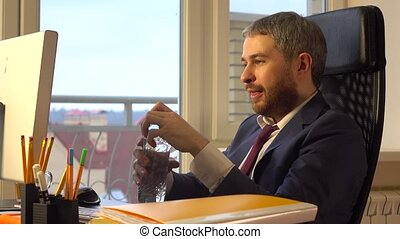 Young confident businessman drinking water at his desk.