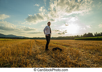 Young confident businessman standing in sawn field