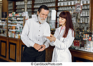 Young confident cheerful Caucasian woman pharmacist is recommending safety medicine for senior man client in ancient drugstore. Medicine, healthcare concept.