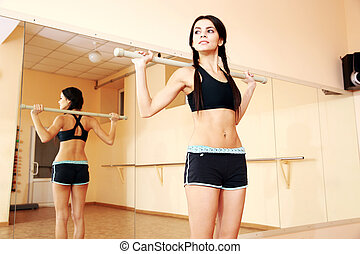 Young confident fit woman working out with gymnastic stick at gym