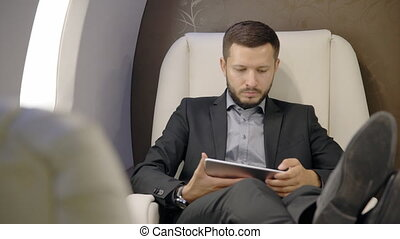 Young confident lawyer businessman is using tablet sitting...