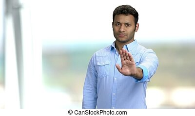 Young confident man making gesture STOP with hand. Handsome Indian guy saying no with hand sign on blurred background. Defence or restriction.