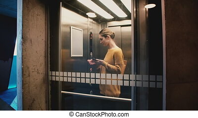 Young confident woman enters elevator, pushes button, door closes and she rides down using smartphone mobile office app.