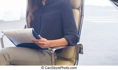 Young confident woman sitting in white comfortable chair