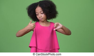 Young confused African girl with Afro hair choosing between thumbs up or thumbs down