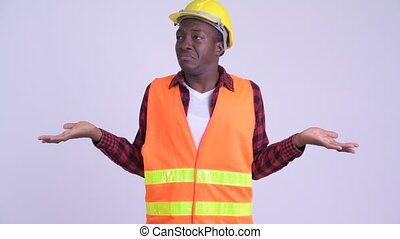 Young confused African man construction worker shrugging shoulders